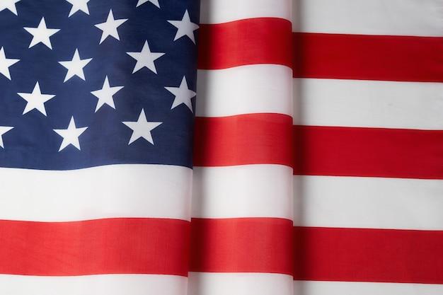 Gebogene flagge der satinbeschaffenheit der usa. gedenktag oder 4. juli.