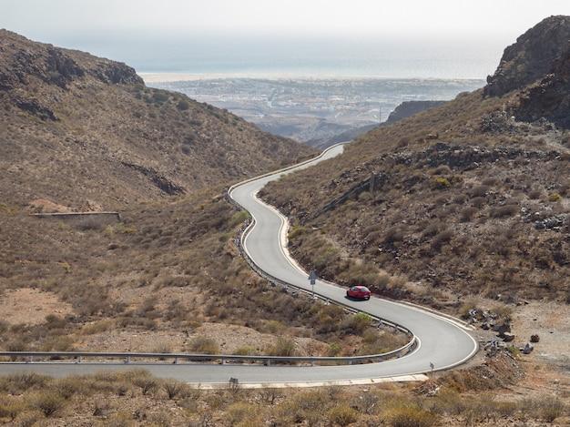 Gebogene kurvenreiche straße mit einem roten auto in den bergen in gran canaria