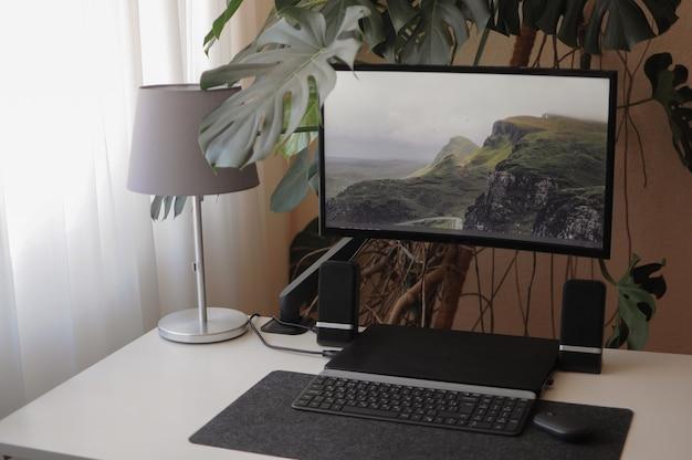 Gebogener großer bildschirm mit laptop. stilvoller und moderner arbeitsplatz zu hause mit zimmerpflanzen
