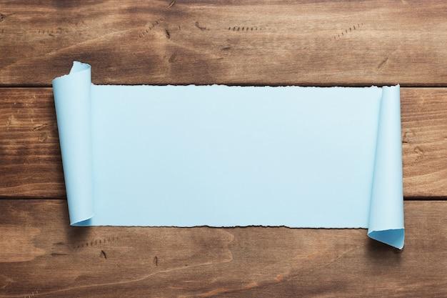 Gebogenes oder gescrolltes papier auf hölzerner hintergrundtextur