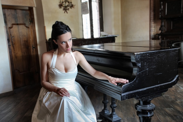 Gebohrte elegante frau nahe bei einem klavier
