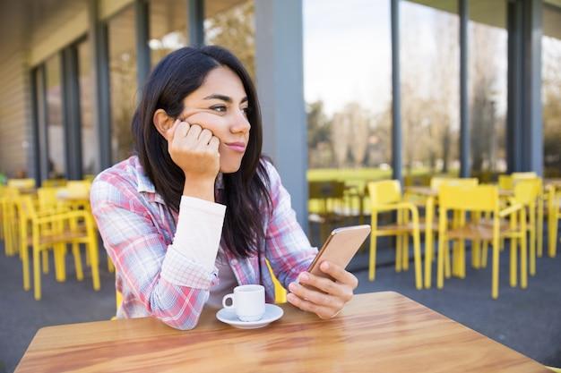 Gebohrte frau, die im straßencafé mit smartphone und kaffee sitzt