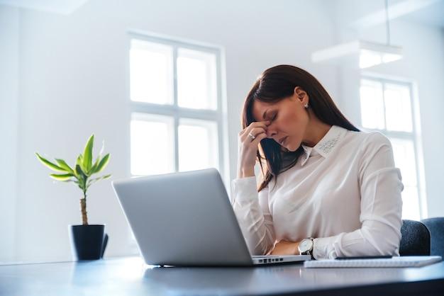 Gebohrte junge frau im büro, das mit einem laptop arbeitet