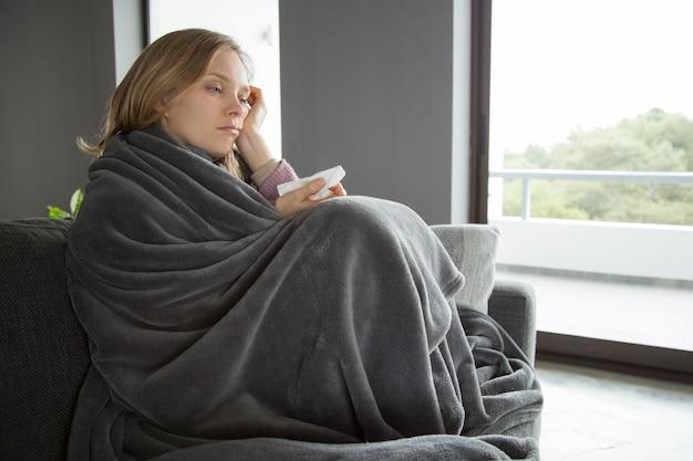 Gebohrte kranke frau, die hand auf kopf, serviette in einer anderen hält
