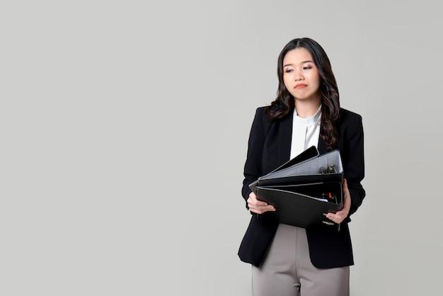 Gebohrte unglückliche asiatische geschäftsfrau, die dokumentdateien verwahrt