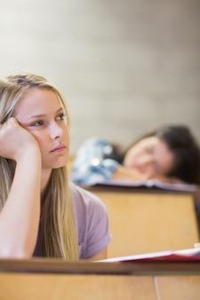 Gebohrter hörender student während mitschüler, der in der universität schläft