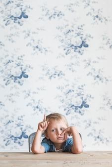 Gebohrter kleiner junge, der auf dem stuhl aufwärts zeigt finger sitzt