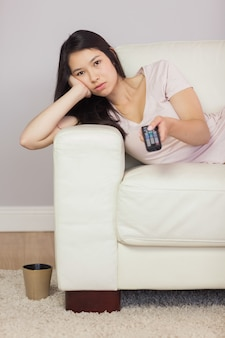 Gebohrtes asiatisches mädchen, das auf dem sofa liegt, das fernsieht
