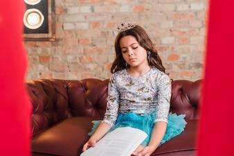 Gebohrtes Mädchen, das auf Sofa an der Bühne hinter dem Vorhang mit Indexen sitzt