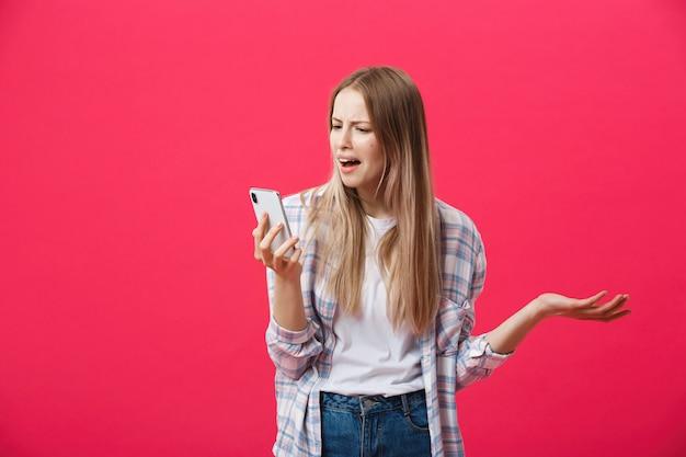 Gebohrtes mädchen, das um das telefon ersucht und auf einem rosa hintergrund verrückt schaut