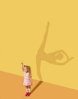 Geboren, um emotionen zu verursachen. kindheits- und traumkonzept. konzeptbild mit kind. der schatten an der studiowand ist von mir gemalt. kleines mädchen will ballerina, balletttänzerin, künstlerin im theater werden.