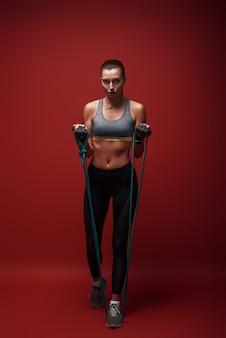 Geboren, um schöne sportlerin zu gewinnen, führt übungen mit widerstandsband durch
