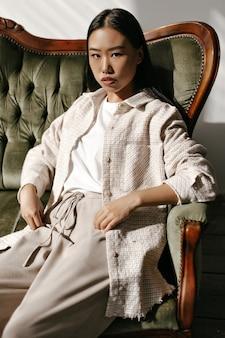 Gebräunte attraktive asiatin in karierter beigefarbener strickjacke, hose und weißem t-shirt schaut in die kamera und sitzt auf einem samtgrünen sofa