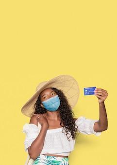 Gebräunte frau, die ihre sommerferien mit einer kreditkarte genießt