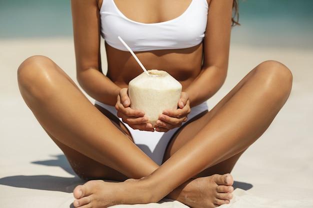 Gebräunte frau im bikini mit kokosnuss am strand