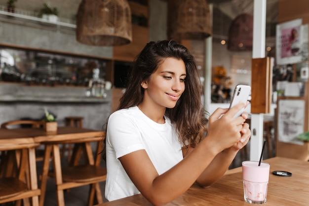 Gebräunte frau im weißen t-shirt schaut in telefonbildschirm