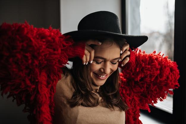 Gebräunte frau in guter stimmung posiert am fenster. foto der dame im roten strickpullover und im schwarzen hut.