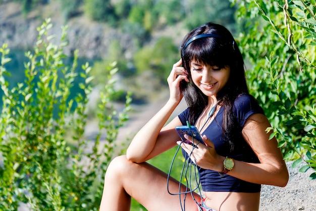 Gebräunte frau mit kopfhörern, die musik draußen hören
