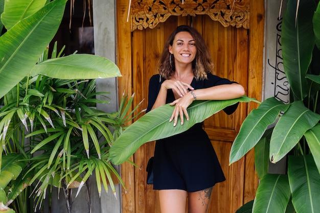 Gebräunte frau mit kurzen lockigen haaren in schwarzen sexy overalls durch tür der tropischen villa im urlaub bei sonnenuntergangslicht