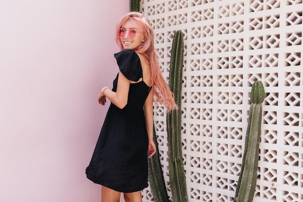 Gebräunte frau mit rosa haaren, die neben kaktus lächeln.