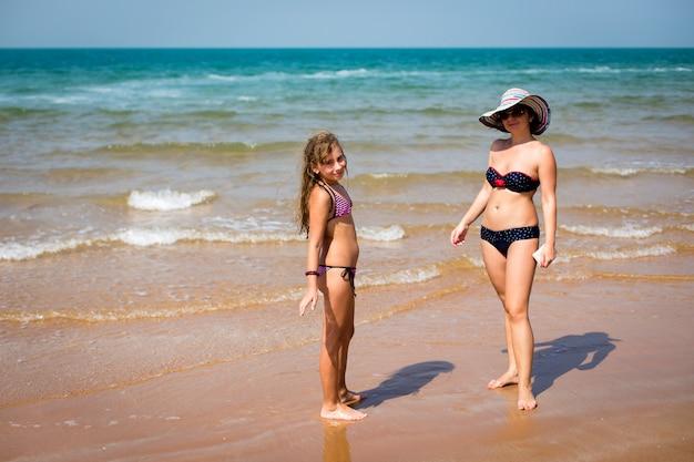 Gebräunte frau und ein mädchen am strand stehen