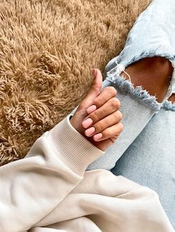 Gebräunte hand einer frau mit einer sanften beige-rosa maniküre, die mit gelpolitur bedeckt ist