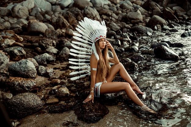 Gebräunte junge bohoartfrauen mit weißem großem federhut und greller tätowierung, die felsigen strand sitzt. stil und themenurlaub