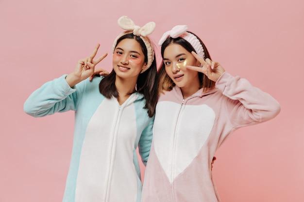 Gebräunte junge brünette mädchen in weichen bunten kigurumis und stirnbändern zeigen friedenszeichen und posieren mit kosmetischen augenklappen