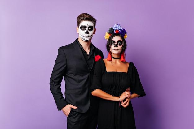 Gebräunte junge frau im zombiekostüm, die fotoshooting mit freund genießt. lustiges paar in halloween-kleidung posiert