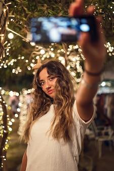 Gebräunte kaukasische frau, die ein selfie an einem vergnügungspark nimmt