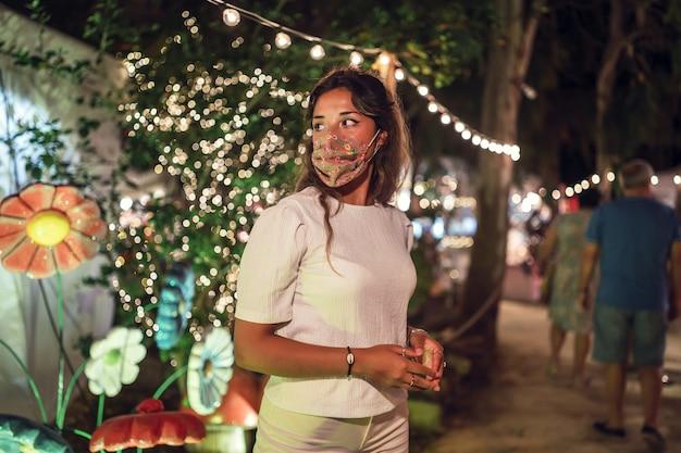 Gebräunte kaukasische frau, die eine blumenmaske an einem vergnügungspark trägt