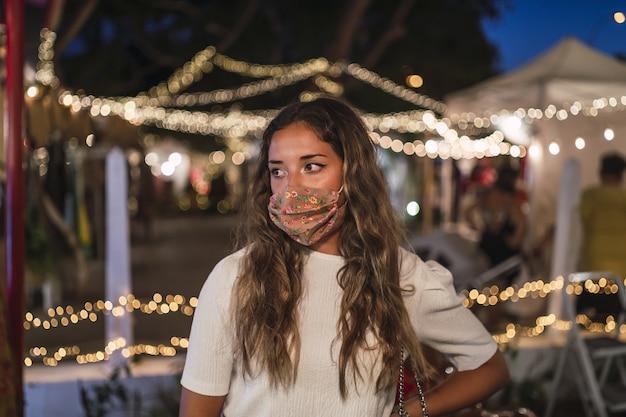 Gebräunte kaukasische frau, die eine blumenmaske in einem vergnügungspark trägt
