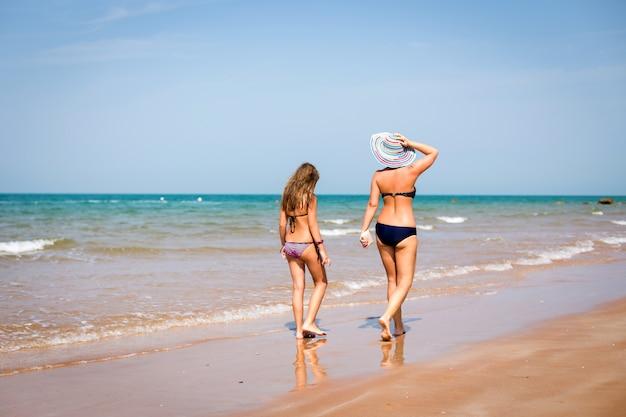 Gebräunte mutter und tochter zu fuß am strand