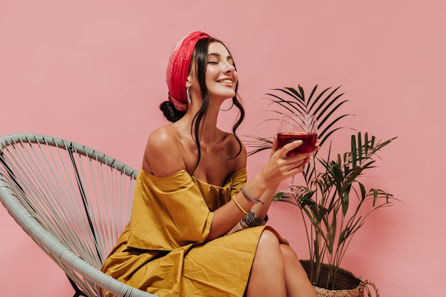 Gebräunte schlanke dame mit welligem haar in hellgelbem outfit und accessoires, die mit geschlossenen augen lächelt und mit einem glas rotwein posiert
