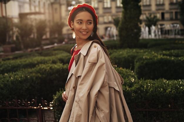 Gebräunte schöne brünette frau in roter stilvoller baskenmütze und trendigem beigem trenchcoat lächelt, schaut zurück und geht im park spazieren