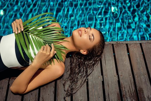 Gebräunte schönheit mit nassen haaren liegt in der nähe des pools mit einem grünen blatt. spa- und entspannungskonzept