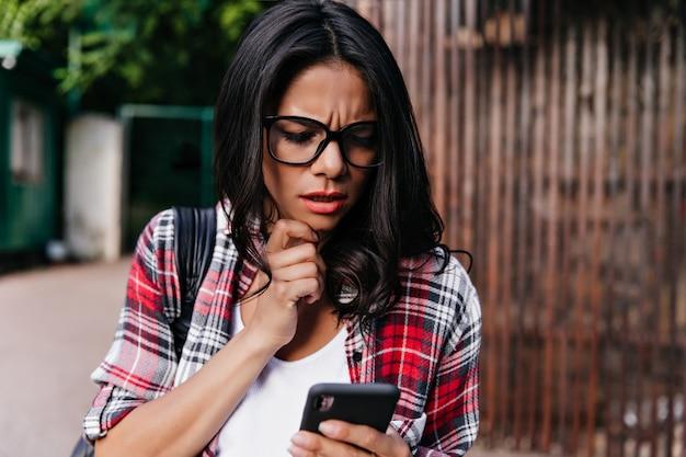Gebräunte unglückliche frau in den gläsern, die auf der straße mit telefon stehen. schönes ernstes mädchen las nachricht.