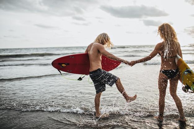 Gebräunter mann und frau halten hand, halten surfbretter und spritzen wasser