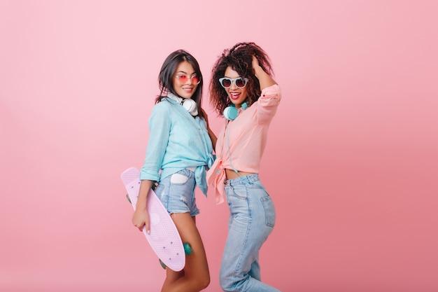Gebräuntes ernstes asiatisches mädchen in der rosa sonnenbrille, die mit afrikanischem lockigem freund steht und skateboard hält. stilvolle sportliche mulattin in jeans mit kopfhörern, die mit haaren spielen