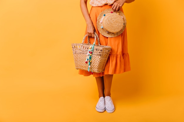Gebräuntes mädchen im orangefarbenen rock und in den weißen schuhen, die auf gelb stehen. spektakuläres weibliches modell mit trendigem hut, der im studio aufwirft.