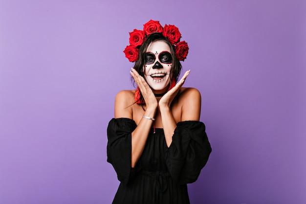 Gebräuntes mädchen im schwarzen kleid mit nackten schultern in überraschung. innenporträt des jungen mexikanischen modells mit make-up für halloween und blumen in ihren haaren