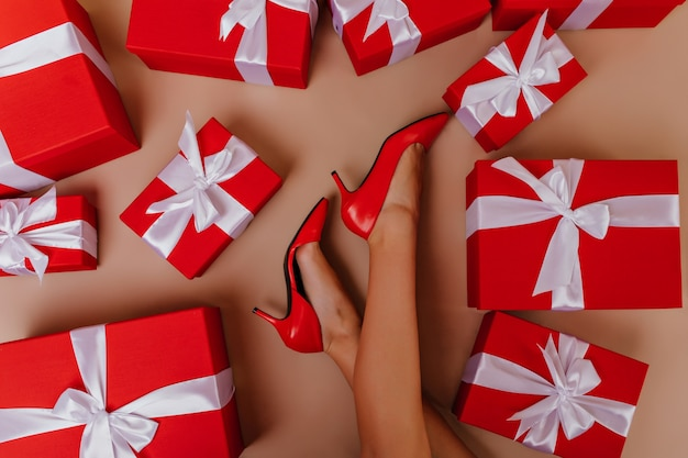 Gebräuntes mädchen in den roten schuhen, die nach neujahrsparty aufwerfen. glamouröses weibliches modell, das auf dem boden mit geschenken sitzt.