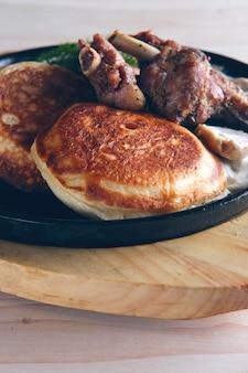 Gebraten in ofenkaninchen mit krapfen und zwiebelsauce. roheisenwanne auf hölzernem schneidebrett und glas mit moosbeersaft