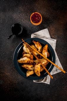 Gebratene asiatische mehlklöße gyoza auf dunkler platte dienten mit essstäbchen und sojasoße