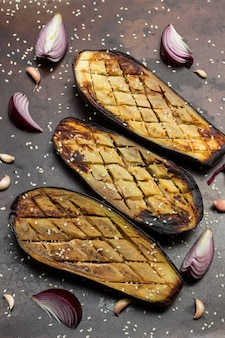 Gebratene auberginen mit sesam, zwiebeln und knoblauch. rostiger metallhintergrund. flach liegen