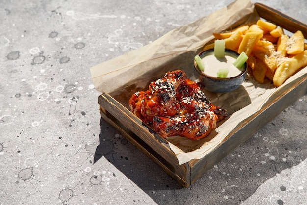 Gebratene beine, trommelstöcke in honig-senf-sauce und pommes-frites-kartoffeln mit salz und sauce auf steinhintergrund. flache lage, draufsicht, platz für text