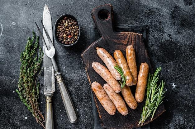 Gebratene bratwurst oder hot dogs würstchen auf einem holzbrett. draufsicht.
