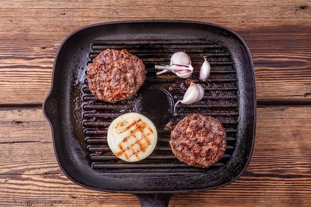Gebratene burger-rindfleischkoteletts mit zwiebel und knoblauch auf grillwanne auf hölzernem hintergrund