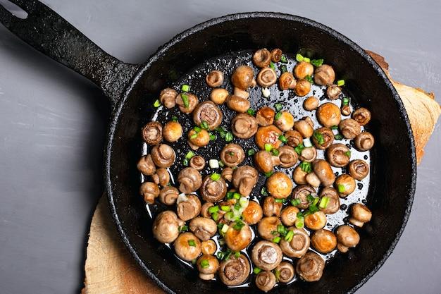 Gebratene champignons champignons mit kräutern in einer schwarzen pfanne auf einem grauen hintergrund flach liegen draufsicht.