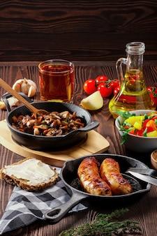 Gebratene champignons und ei in gusseisenpfanne. bestandteile zum rustikales frühstück auf holztisch.